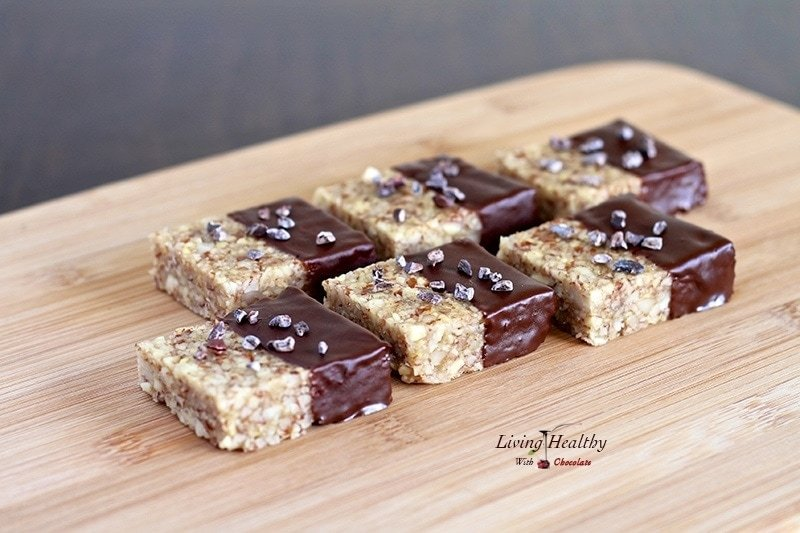 wooden cutting board with several paleo nut krispy treats lined up
