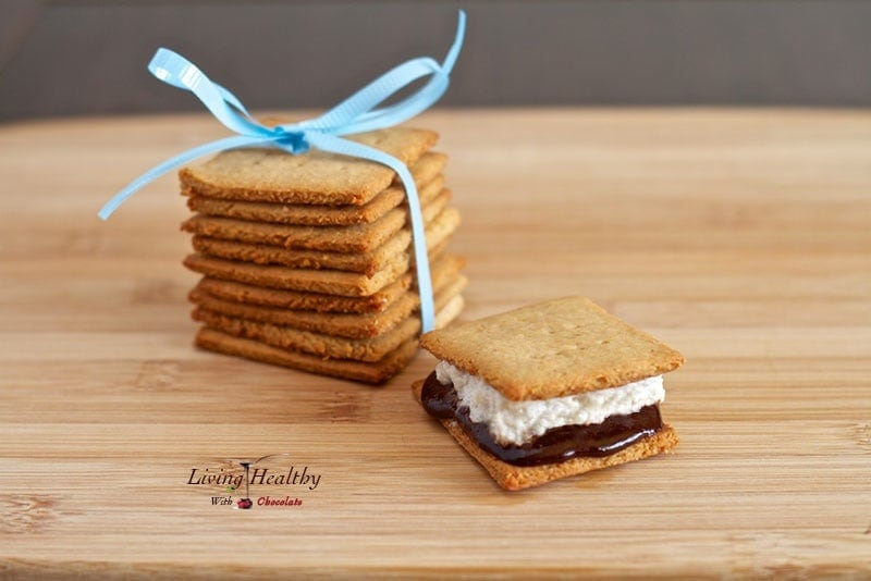 wooden cutting board with one paleo s\'mores dessert treat with stack of homemade graham crackers with blue bow