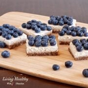 wooden cutting board topped with several pieces of blueberry coconut cream pie squares with lots of blueberries on top of each