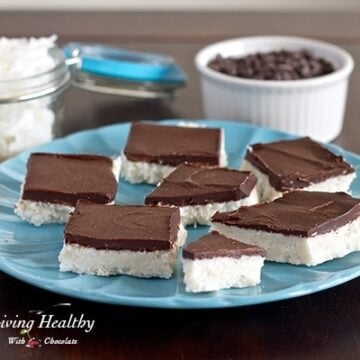 blue plate topped with numerous paleo coconut bark bars topped with chocolate and more chocolate and coconut in jars behind