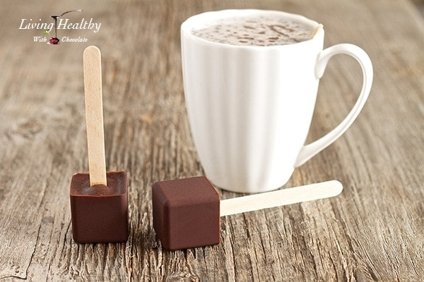 close up of paleo hot chocolate on a popsicle stick with glass of milk in background