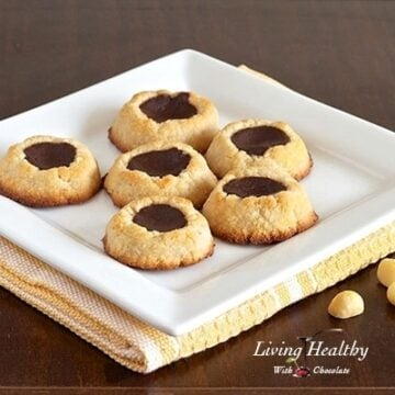 square plate with six paleo macadamia nut chocolate filled thumbprint cookies on wooden table