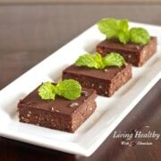 narrow white dish with three no bake mint dark chocolate brownie squares topped with fresh mint