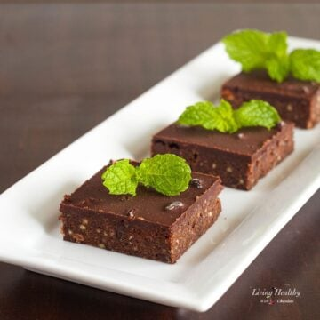 three no-bake mint dark chocolate brownies topped with fresh mint