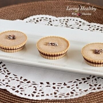 three paleo inside out almond butter cups on a white rectangular with white lace placemat underneath