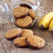 glass jar on its side filled with banana cinnamon cookies with several in front of jar and two bananas on right side of jar