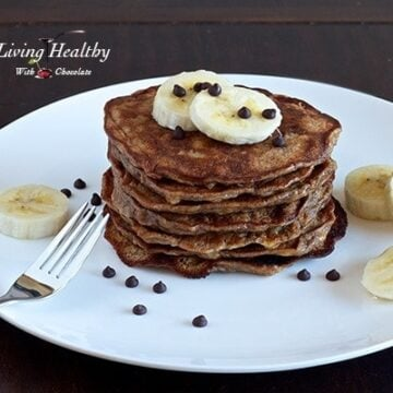 stack of paleo banana pancakes topped with slices of banana on a large white plate on wooden table