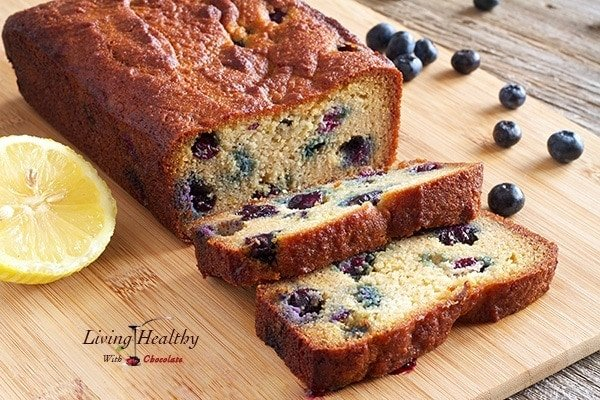 close up of paleo blueberry bread loaf with lemon glaze on cutting board with loose blueberries in background