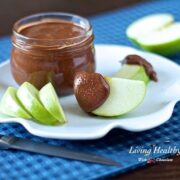 jar of paleo chocolate almond butter with slices of green apple on plate with knife in foreground on blue placemat