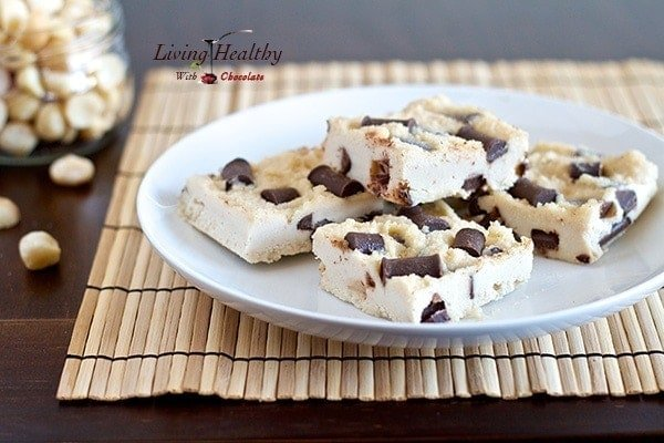 plate of chocolate chunk macadamia nut fudge bars topped with chocolate chips