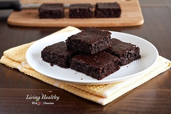 plate sitting on yellow napkin with a stack of flourless chocolate brownies and more brownies on cutting board in background