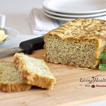 loaf of paleo pesto cheese bread with two slices cut on a cutting board with knife and plates in background