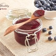 glass jar of sugar free blueberry butter with wooden spoon on top and bowl of blueberries in background