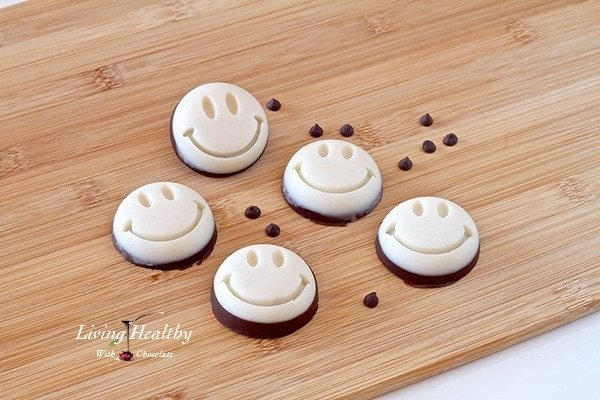 wooden table with five coconut smily treats with some loose chocolate chips scattered between the treats
