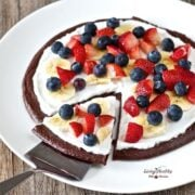 large serving plate with raw chocolate brownie fruit pizza dessert topped with cream and berries with one slice on spatula