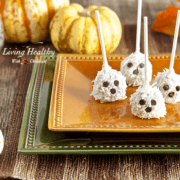halloween dessert ghost truffles with chocolate chip eyes and decretive pumpkins in the background