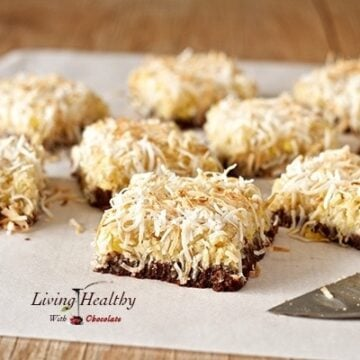 parchment paper on wooden table with numerous square of pineapple coconut dessert bars