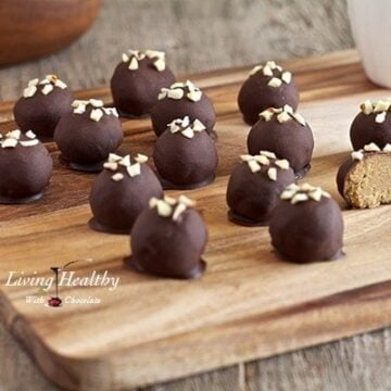 wooden cutting board with numerous paleo peanut butter truffles topped with small pieces of nuts