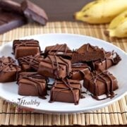 plate with numerous squares of frozen peanut butter Chocolate banana fudge bites drizzled in chocolate