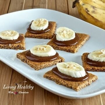 white plate with six paleo graham crackers topped with homemade nutella and a slice of banana and two bananas in background