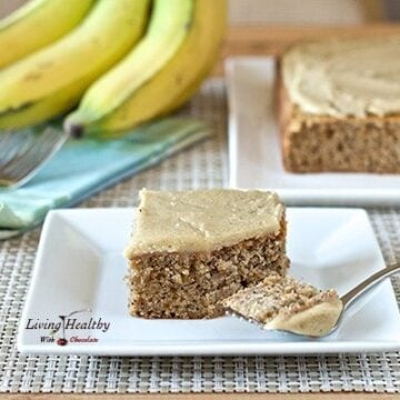 slice of banana poppy seed cake with white chocolate vanilla bean frosting on plate with more cake bananas in background