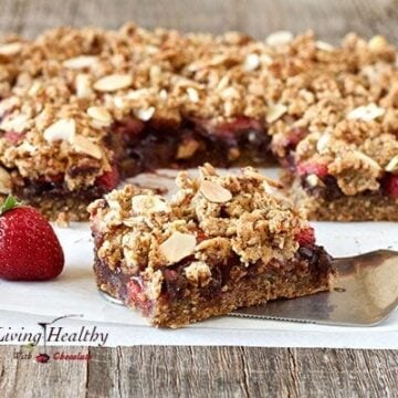 close up of a square piece of a paleo chocolate strawberry crumble bar with larger portion in background