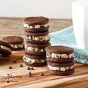 stacks of homemade paleo cookie dough Oreos on wooden table with glass of milk in background