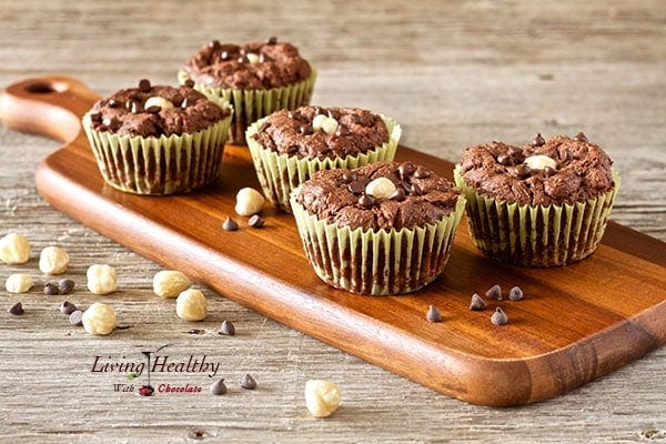 five chocolate hazelnut nutella muffins on cutting board with loose nuts sprinkled on and around cutting board