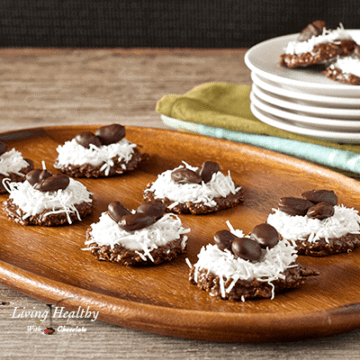 wooden serving tray with six no bake cookies topped with coconut and a stack of plates with more cookies in background