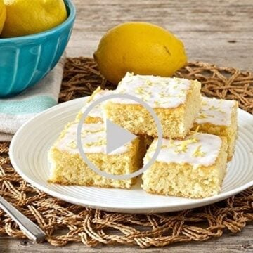 plate of paleo lemon brownies with coconut lemon glaze with lemons on a blue bowl in background