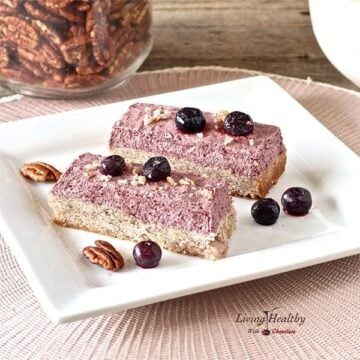 two blueberry breakfast bars on a white plate with loose berries on top and a jar of pecans in background