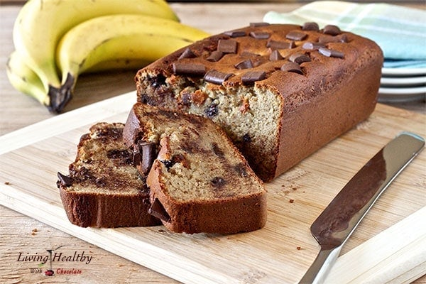 loaf of peanut butter cup banana bread with two slices cut and bananas in background