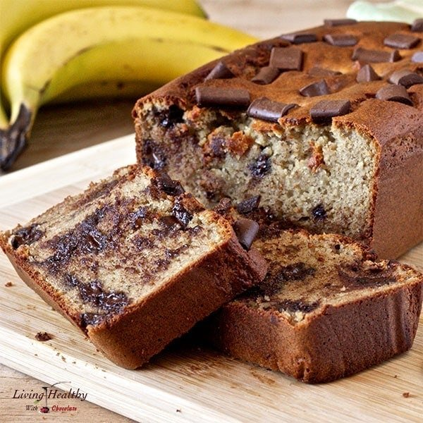 close up of loaf of peanut butter cup banana bread with two slices cut and bananas in background