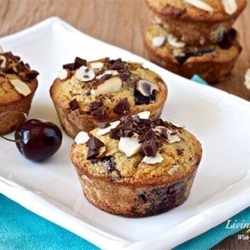 three dark chocolate cherry almond muffins on a white plate with more muffins stacked in background