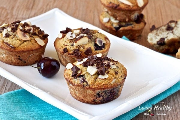three cherry muffins on a plate topped with chocolate chunks and sliced almonds