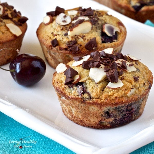close up of two cherry muffins topped with chocolate chunks and sliced almonds on a white plate