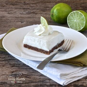 square piece of paleo key lime pie on white plate with fork and two limes in background
