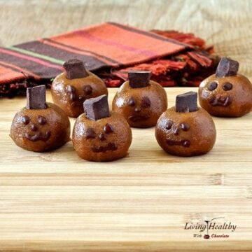 Halloween almond butter pumpkin truffle heads with spooky faces on a wooden table with colorful napkins in background