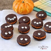assortment of halloween chocolate whoopie pie cookies with pumpkin filling with funny eyes and small pumpkin in background