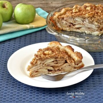slice of homemade apple pie with a white plate and silver fork and glass dish behind with full pie and apples to the left