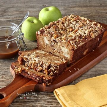 loaf of caramel apple pie bread on wooden cutting board with jar of caramel and two green apples in background