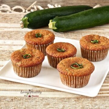 plate of five zucchini muffins on a brown and white place mat with two large zucchini in the background