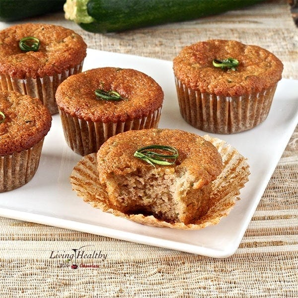 five zucchini muffins on a white plate and one muffins with a bite taken off