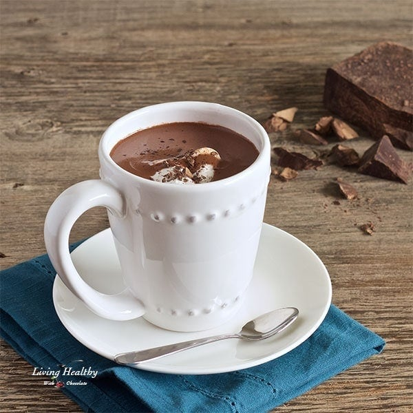 cup of hot chocolate served in white mug with small dish and blue napkin underneath and pieces of chocolate in background