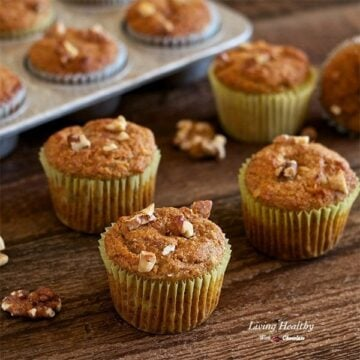 banana walnut muffins on a wooden table with a muffin pan in background filled with muffins