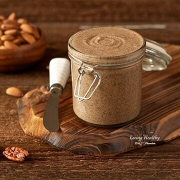 full jar of vanilla cinnamon almond butter on a wooden table with a serving knife and almonds in the background in bowl
