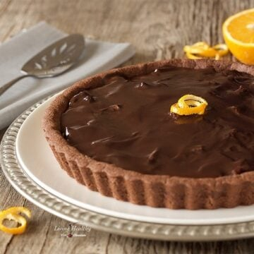 chocolate orange almond tart on a serving plate with orange spirit orange peel and half of an orange in background