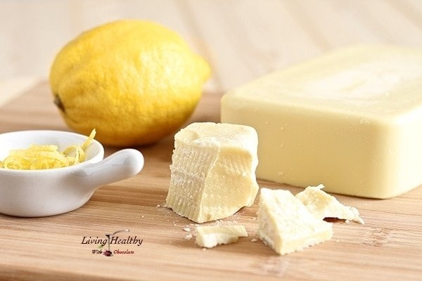 brick of cacao butter with lemon and small dish with shaved lemon zest in background for making white chocolate lemon mousse