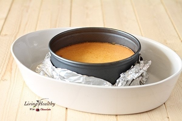 cheesecake base sitting in a round pie dish wrapped in foil resting inside a larger white dish
