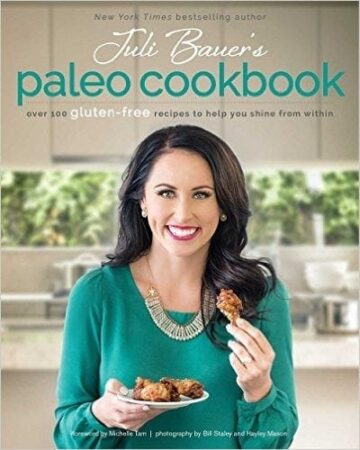 Juli Bauers Paleo cookbook cover with Juli Bauers smiling for the camera holding up some food in her hand